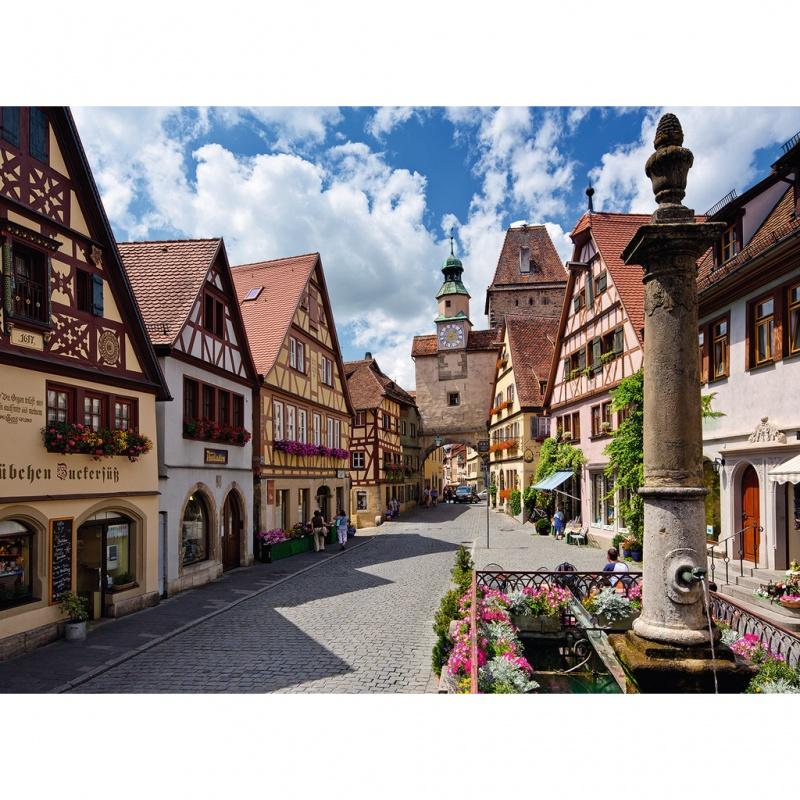 Пазл Ротенбург, 500 элементовРотенбург — примечательный город Германии. Его полное название сможет запомнить не каждый — Ротенбург-об-дер-Таубер. Одна из его улиц изображена на данном пазле, состоящая из 500 деталей из плотного картона. Тут можно увидеть уютные двухэтажные дома с треугольной крышей, украшенные цветами, а также цветочные магазины. На улице стоит ясная погода с белыми облаками. Пазл можно подарить и взрослому человеку, так как в процессе сборки приходят в порядок мысли и очищается разум.<br>